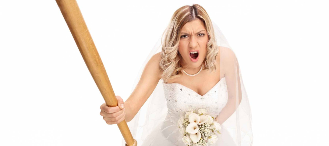 Angry young bride holding a baseball bat and yelling