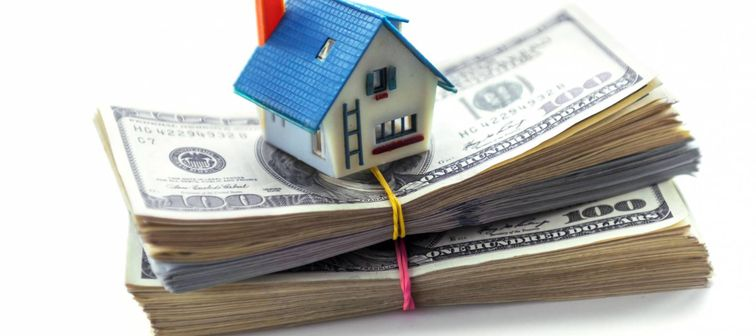 house model on dollar cash stack isolated