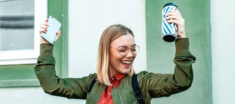 Happy young woman with short blonde hair and glasses holding her smartphone and coffee cup over her head