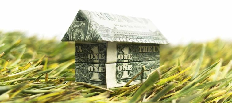 Going green — origami cash house on grass