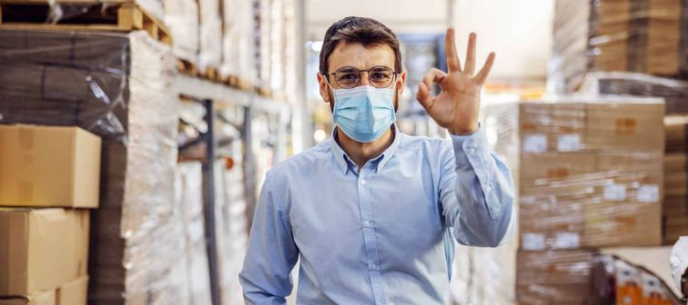 Young businessman with sterile protective mask on standing in warehouse and showing okay sign. Protection from covid-19.