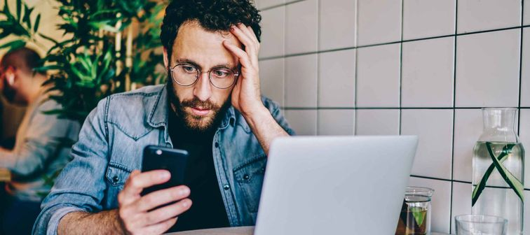 Worried bearded young man reading searching for information about his amended tax return