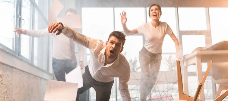 scared businessman falling on floor while running and screaming near coworkers in office with smoke