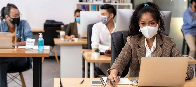 Portrait office workers wear face mask working in new normal office with social distance