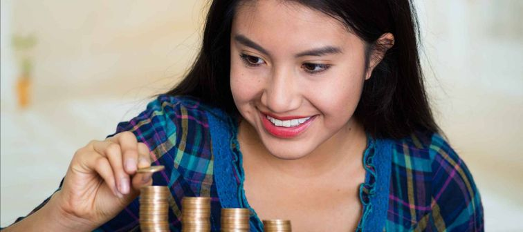 Brunette woman facing camera, stacking coins in piles on desk, smiling happily