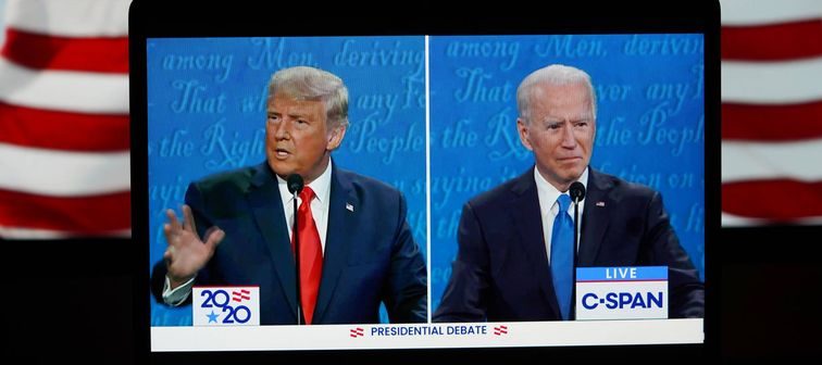 President Trump and Joe Biden at debate, as seen on a split screen tablet with American flag in the background