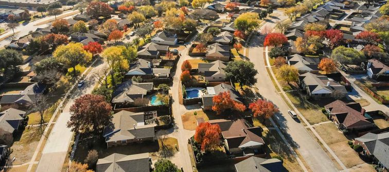 Aerial view beautiful neighborhood in Coppell, Texas, USA in autumn season. Row of single-family home with attached garage, garden, swimming pool surrounded by colorful fall foliage leaves