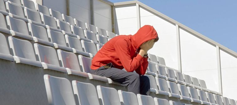 Fan sits in empty stands, hands over face sad
