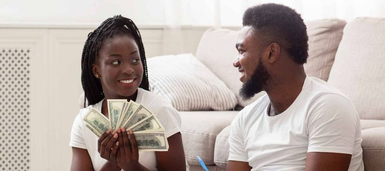 Planning family budget. Happy afro couple sitting on floor at home with dollar cash and notepad, deciding together how to spend money