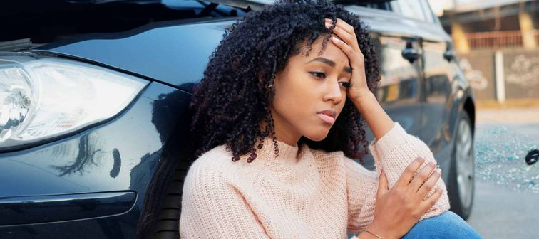 Black woman sits next to vehicle after collision