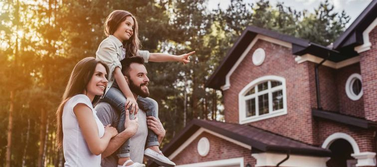 Happy family is standing near their modern house and smiling.