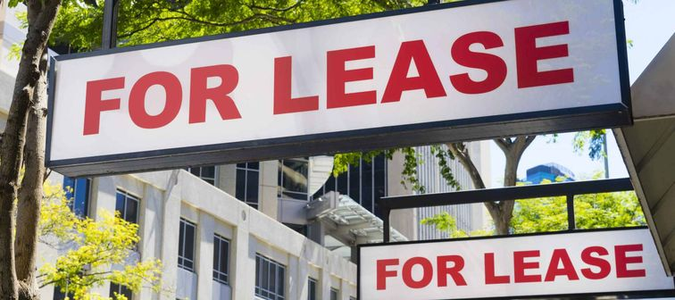 Two For Lease signs on display outside buildings