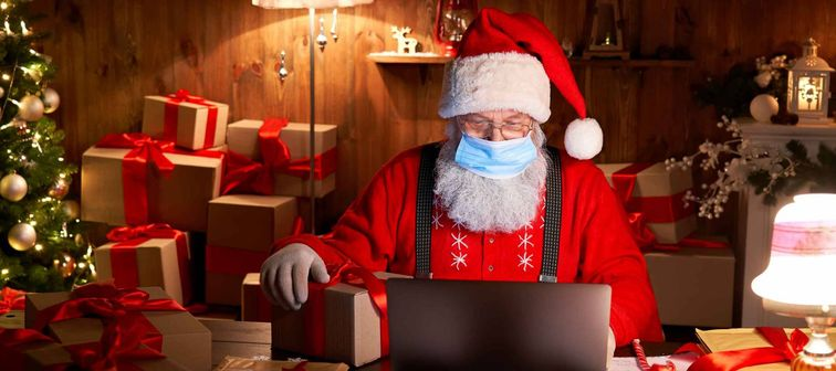 Old bearded Santa Claus wearing face mask, holding gift box on xmas eve sitting at cozy home table late in night using laptop computer