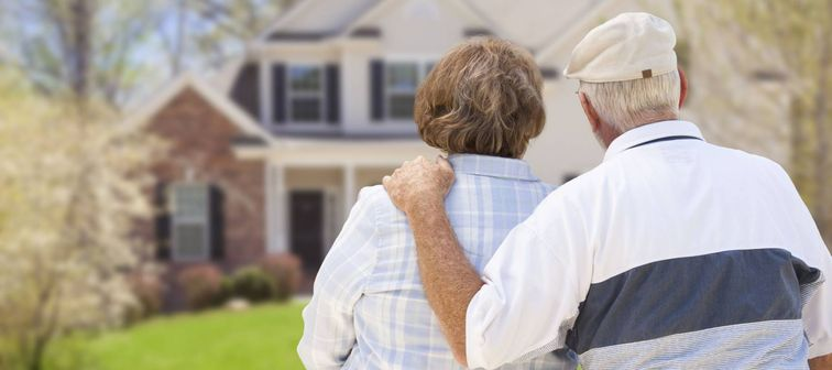A headshot of a happy elderly couple standing in front of a house