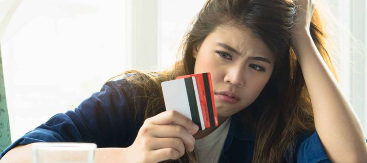 stressed young asian woman trying to find money to pay credit card debt.