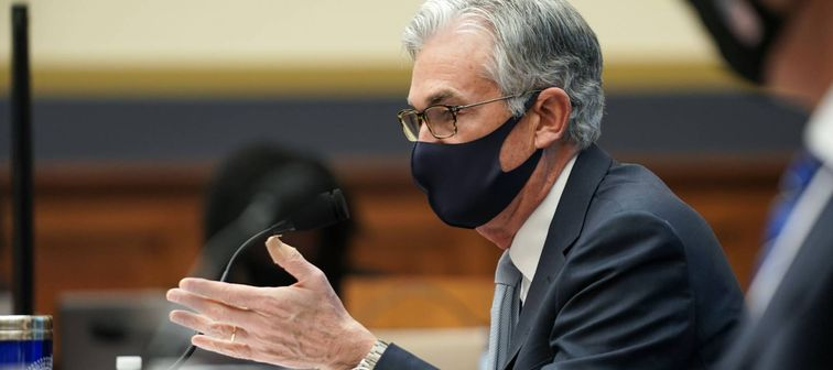 Fed Chairman Jerome Powell wearing mask speaks into microphone