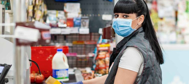 A portrait of young woman in a medical mask and gloves, working at the checkout in a supermarket. Concept of coronovirus, protection from infection and industrial crisis.