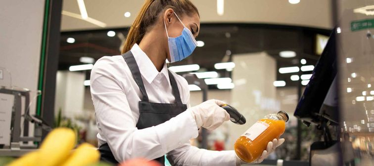 Cashier in supermarket wearing mask and gloves fully protected against corona virus. Working during global virus pandemic.