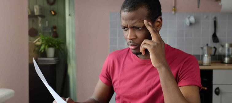 Young frustrated unhappy tired african american man with financial troubles, sitting at kitchen table with papers and calculator, reading documents