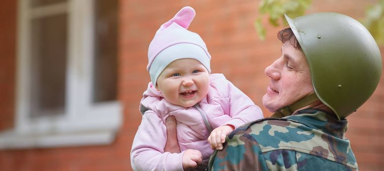 Military man in a helmet with a smiling little baby in his arms.