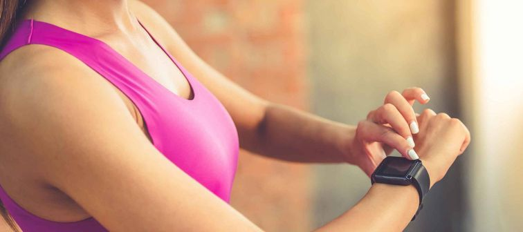 Cropped image of woman in athletic wear looking at a fitness tracker on her wrist