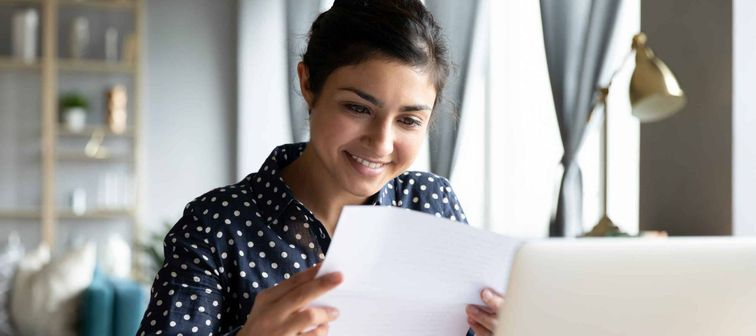 Smiling young woman holding paper while sitting in front of a laptop,