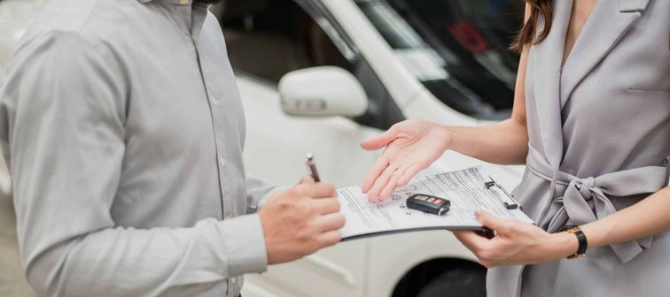 Man signing clipboard that was handed to him by woman, standing in front of car