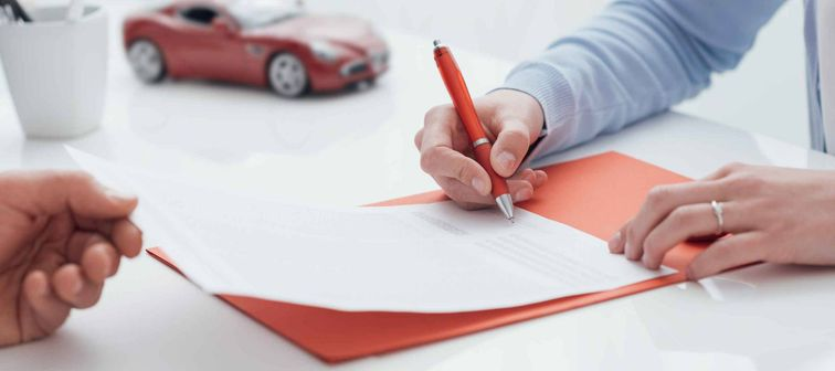 Woman signing auto insurance policy, while man holds the sheet