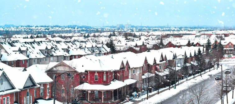 Rooftops of a small town in winter during snowfall.