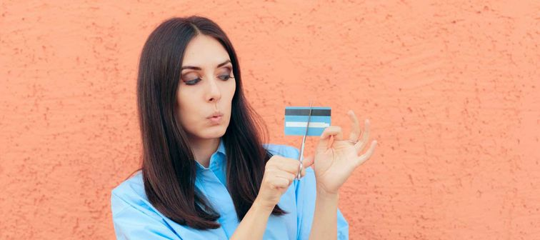 Woman Cutting Credit Card in Half with Scissors. Millennial girl having financial problems for spending too much money