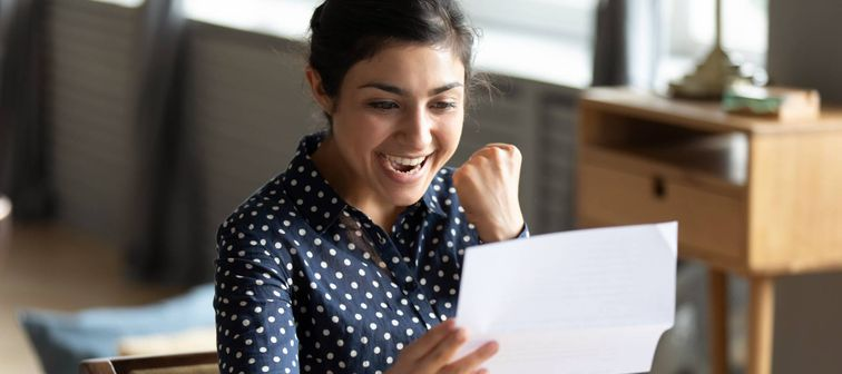 Excited young indian woman holding paper document