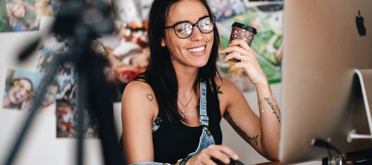 Hipster woman holding coffee cup working at computer