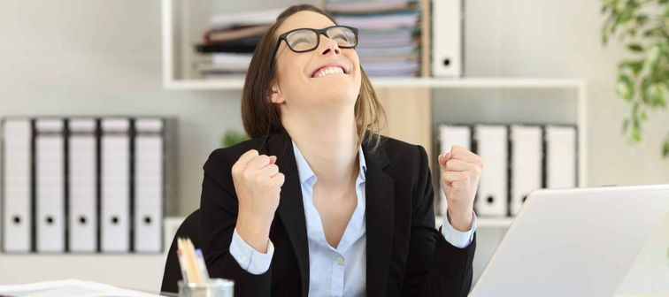 Excited businesswoman celebrating success looking above at office