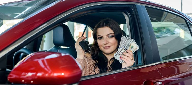 Woman sitting in new car and showing dollars and keys