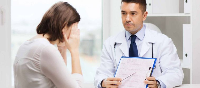 medicine, health care and people concept - doctor with clipboard and young woman meeting at hospital
