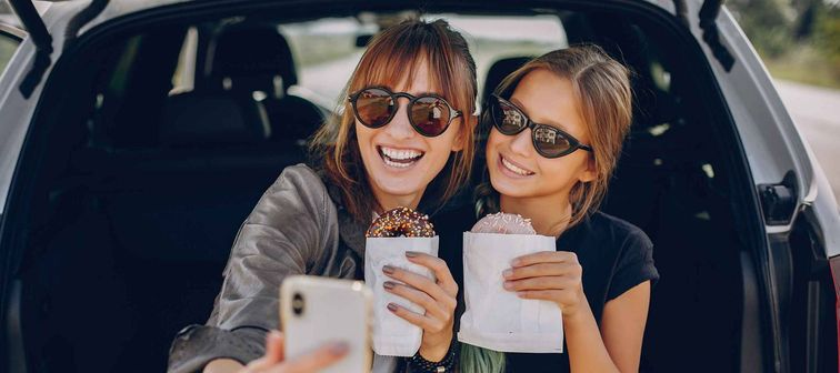 Two young women sitting in the back of a car, wearing sunglasses and posing for a selfie with donuts
