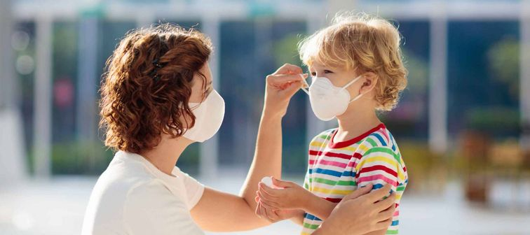 Mother putting on face mask on young child