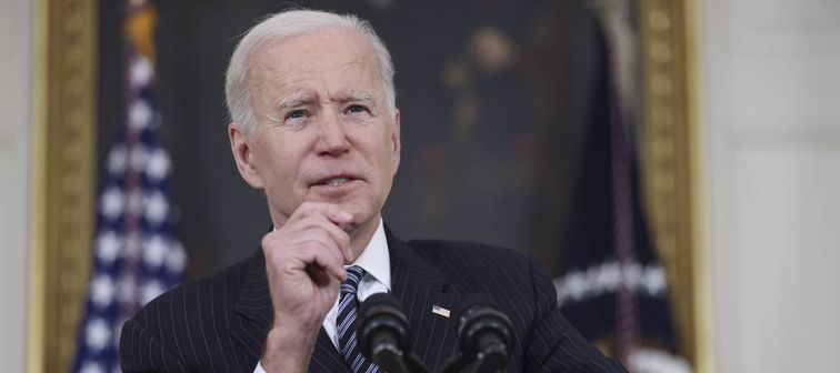 President Joe Biden speaks at a podium with his hand up, making a gesture