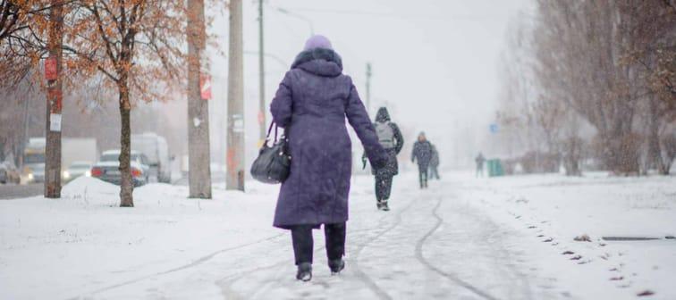 elderly woman in dark coat walks along road that is not snowed off in city. Poor utilities work. Not working snow equipment. Heavy blizzard and snowfall in city.
