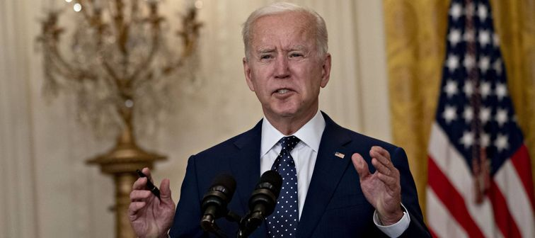 Joe Biden speaks at podium, with open mouth and hands up
