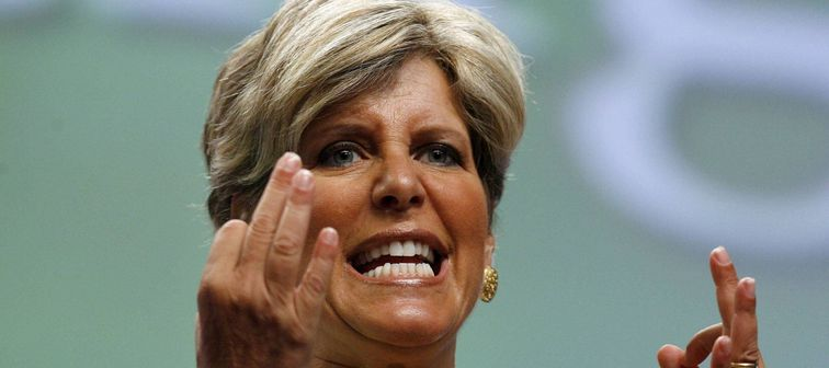Suze Orman holds her hands up and makes an aggressive face