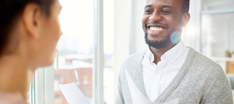 Happy office staff with papers looking at colleague with smile during discussion