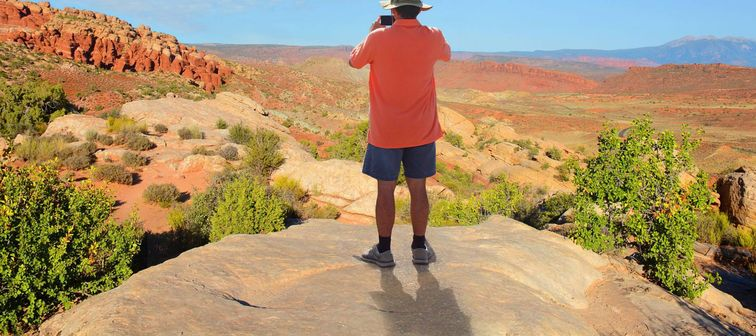 Man standing on top of the mountain taking photos ,looking at beautiful autumn mountains landscape. Moab, Utah, Arches National Park.