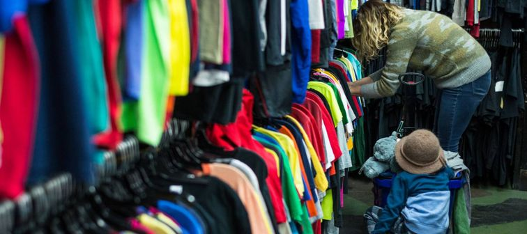 Woman and child browsing through clothing in a thrift store