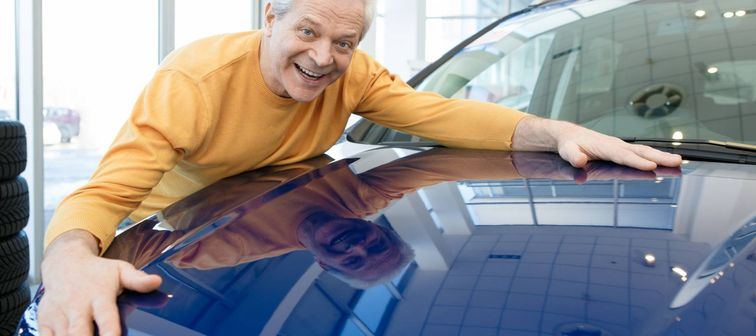 Excited senior man smiling joyfully hugging his newly bought automobile