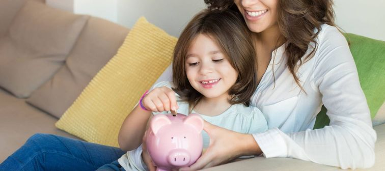 Mother and daughter putting coins into piggy bank while sitting on sofa