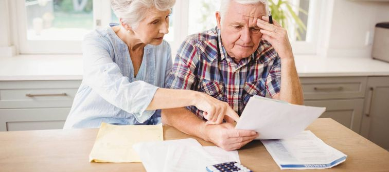 Worried senior couple checking their bills at home