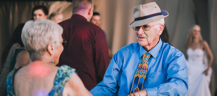 Two active seniors dance on the dance floor at a wedding during sunset.
