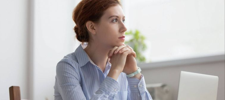 Lost in thoughts woman sits at workplace desk in office in front of laptop
