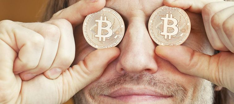 Bearded man holding symbolic bitcoins over his eyes